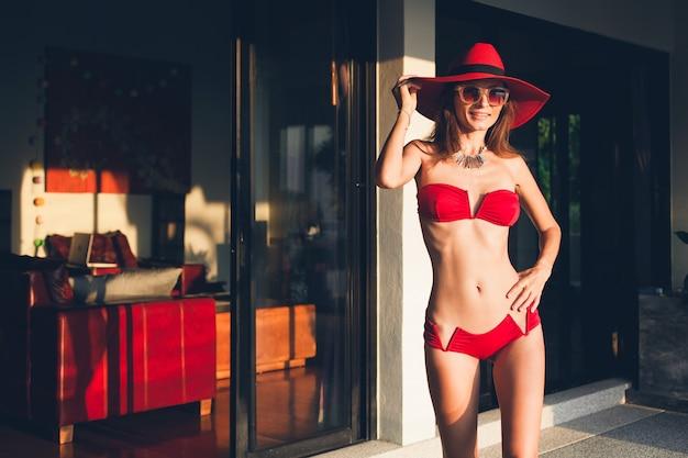 Jeune femme avec un beau corps mince portant un maillot de bain bikini rouge, un chapeau de paille et des lunettes de soleil se détendre sur la station balnéaire tropicale pendant les vacances en asie, silhouette maigre, accessoires tendance de style d'été