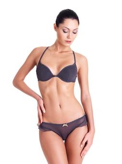 Jeune femme avec beau corps parfait mince en bikini fond blanc isolé