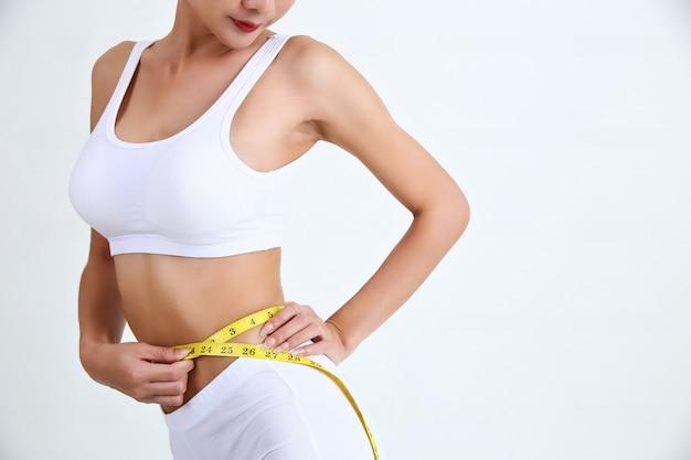 Jeune femme avec un beau corps et ruban à mesurer