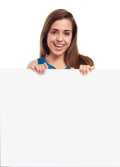 Jeune femme avec un beau sourire posant avec une affiche vide