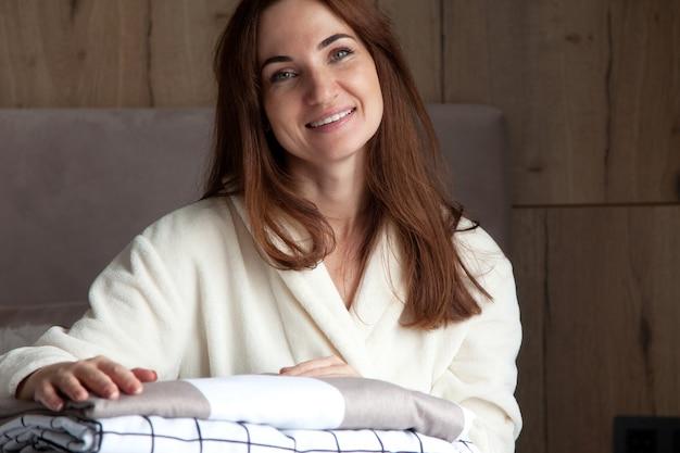 Jeune femme avec un beau sourire en robe beige chaude s'appuie sur une pile de draps pliés de texture différente. literie en coton naturel et biologique. copiez l'espace. fabrication. industrie hôtelière.