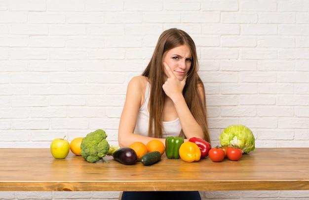 Jeune femme avec beaucoup de légumes debout et pense à une idée