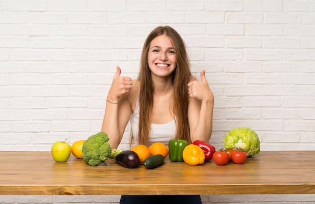 Jeune femme avec beaucoup de légumes donnant un geste du pouce levé