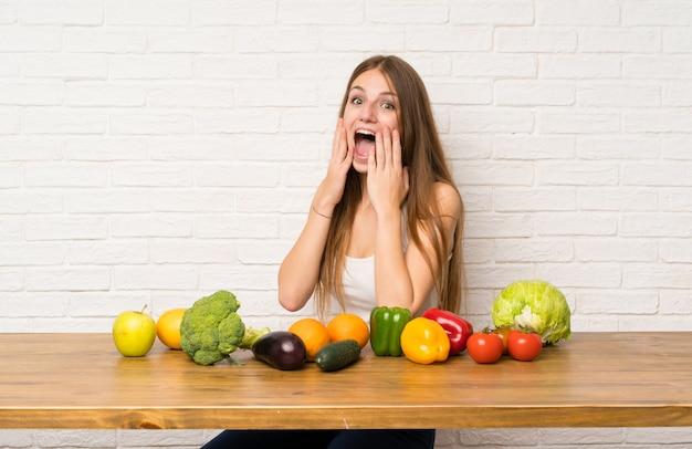 Jeune femme avec beaucoup de légumes avec une expression faciale surprise