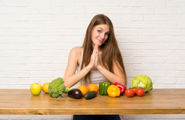 Jeune femme avec beaucoup de légumes implorant