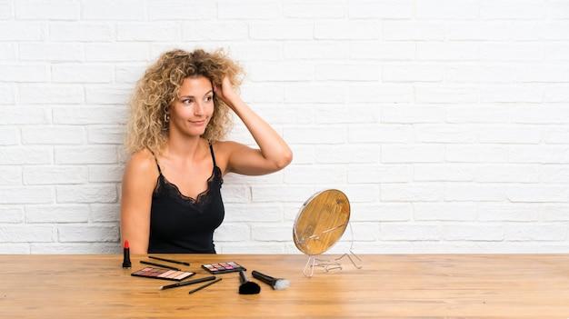 Jeune femme avec beaucoup de pinceau de maquillage dans une table ayant des doutes et avec une expression du visage confuse