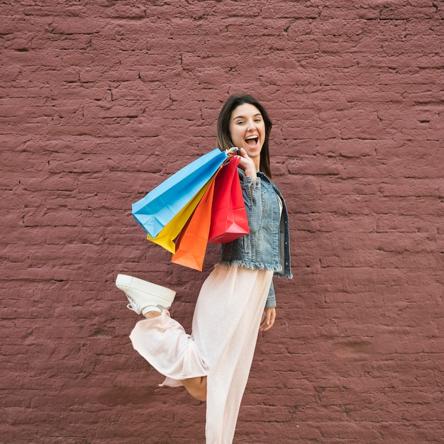 Jeune femme avec beaucoup de sacs shopping lumineux près du mur de briques
