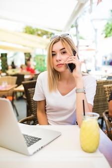 Jeune femme beauté parle avec le patron via téléphone portable