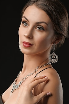 Jeune femme avec de beaux bijoux sur fond noir