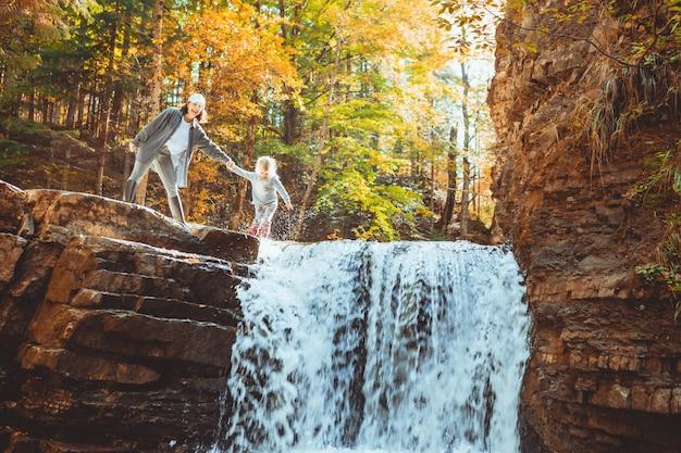 Jeune femme avec bébé fille regardant la cascade au concept de randonnée en forêt d'automne