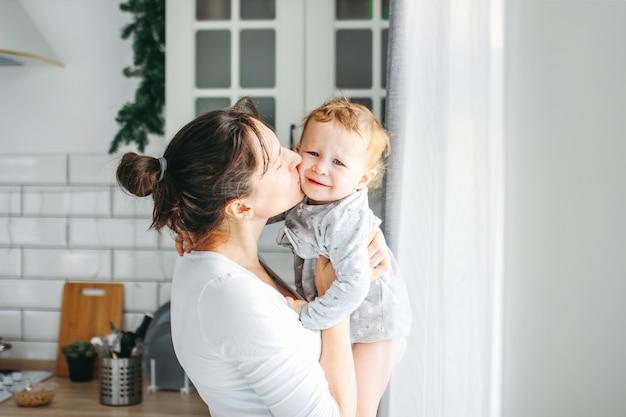 Jeune femme avec bébé sur les mains s'amuser et cuisiner le petit déjeuner à la maison
