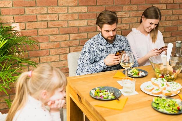 Jeune femme et bel homme assis à table