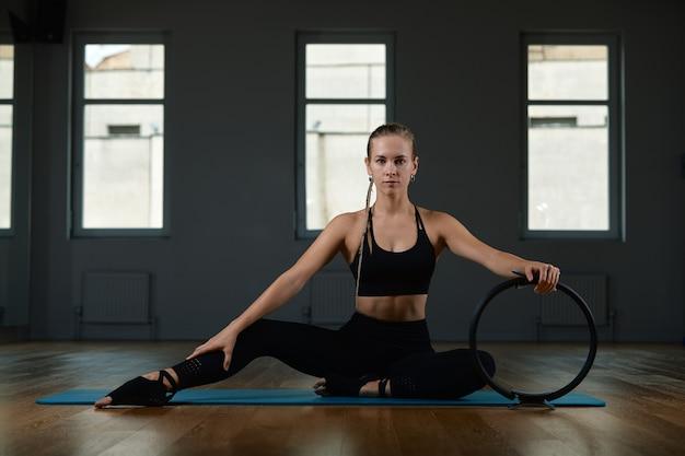 Une jeune femme belle et athlétique fait des exercices avec un anneau de pilates dans le gymnase. sports femme slave dans un costume noir.