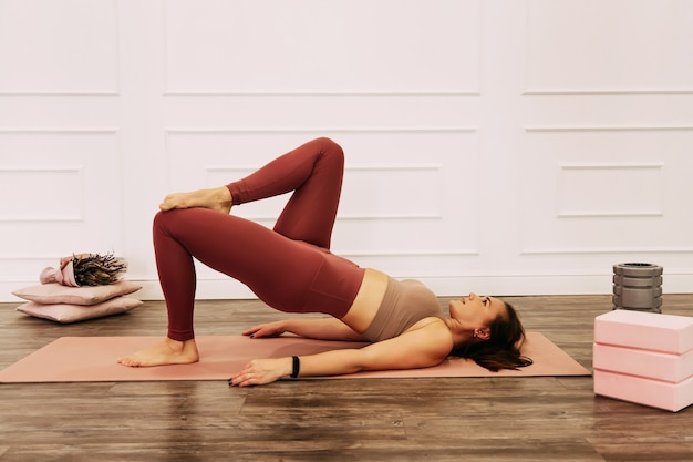 Jeune femme belle en bonne santé en haut sportif et leggings pratiquant le yoga à la maison qui s'étend du corps sur un tapis de yoga souriant détendu avec les yeux fermés, concept de mode de vie sain