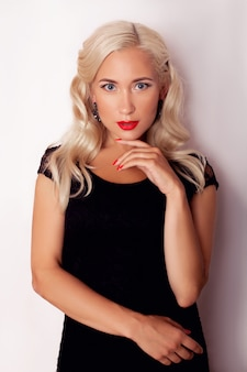Jeune femme belle cheveux blonds en robe noire avec maquillage rétro et coiffure