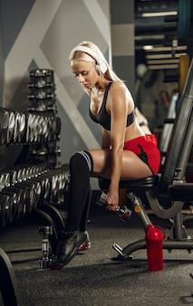 Jeune femme belle formation dans la salle de gym. concept de remise en forme, entraînement, sport, santé