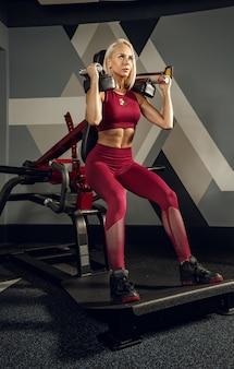 Jeune femme belle formation dans la salle de gym.