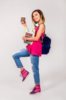 Jeune femme belle hipster, chaussures roses et haut tenant des livres et prendre du café