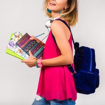 Jeune femme belle hipster, chaussures roses et haut tenant des livres