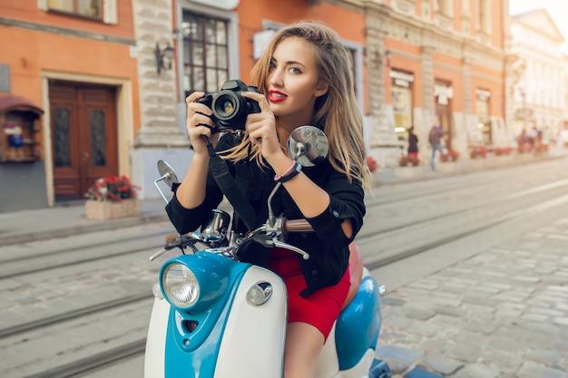 Jeune femme belle hipster équitation avec appareil photo sur la rue de la ville de moto