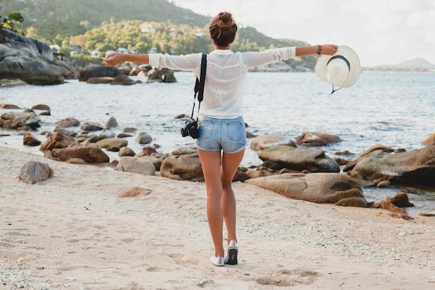 Jeune femme belle hipster en vacances d'été en asie, détente sur la plage tropicale, appareil photo numérique, style boho décontracté, paysage de mer, corps bronzé mince, voyage seul, liberté