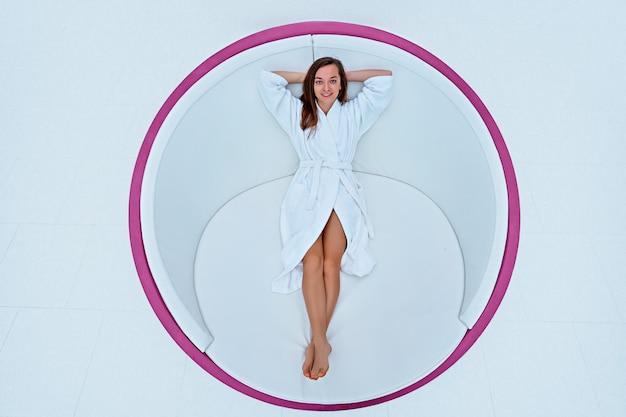 Jeune femme belle joyeuse heureuse portant un peignoir blanc avec les mains derrière la tête, profitant d'un moment de détente dans une station thermale bien-être