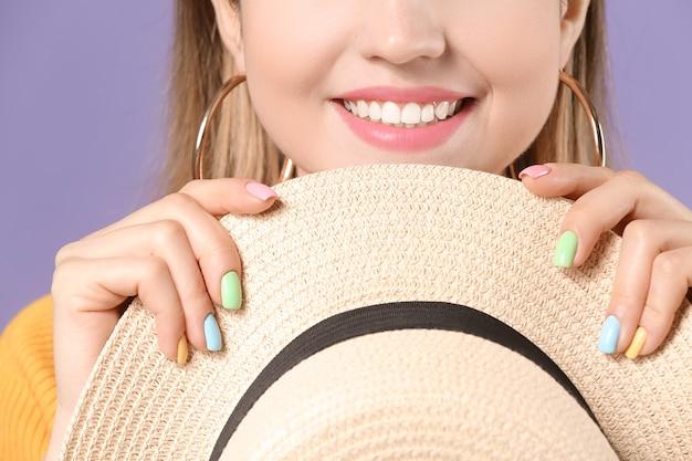 Jeune femme avec une belle manucure sur fond de couleur, gros plan