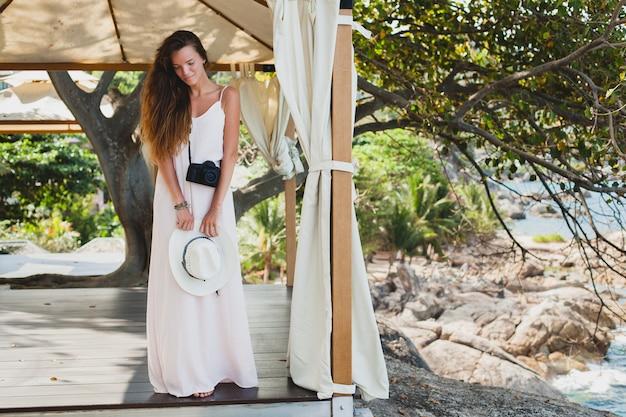 Jeune femme belle naturelle en robe pâle posant sous chapiteau, vacances tropicales, chapeau de paille, tenue d'été sensuelle, resort, style vintage boho
