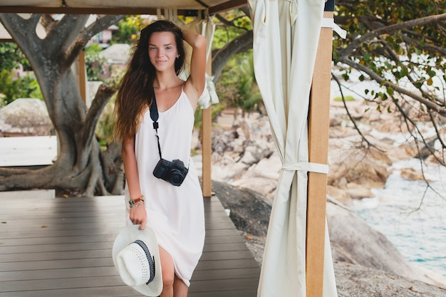 Jeune femme belle naturelle en robe pâle posant sous chapiteau, vacances tropicales,