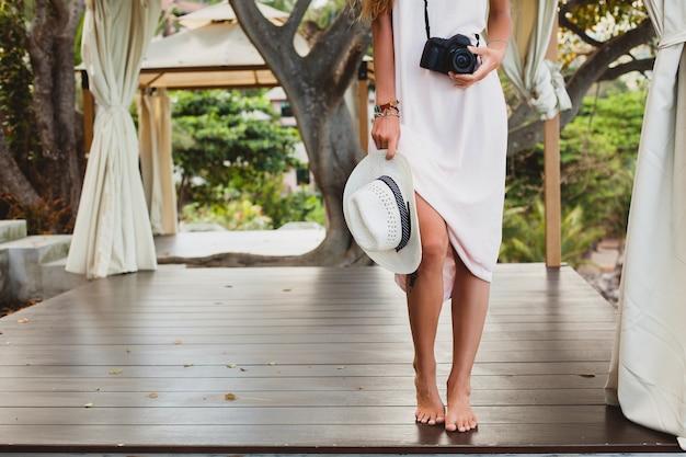 Jeune femme belle naturelle en robe pâle posant, vacances tropicales, chapeau de paille, tenue sensuelle, tenue d'été, resort, style vintage boho, accessoires, jambes