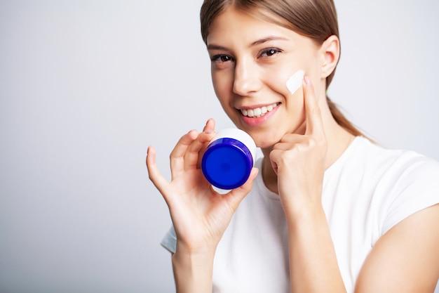 Jeune femme avec une belle peau met de la crème hydratante sur son visage