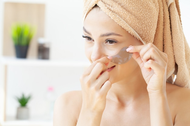 Jeune femme avec une belle peau met des taches noires sur son visage