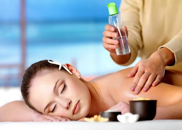 Jeune femme belle relaxante se massage avec de l'huile cosmétique dans un salon spa