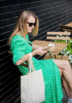 Jeune femme belle avec un sac écologique en lin sur fond de ville