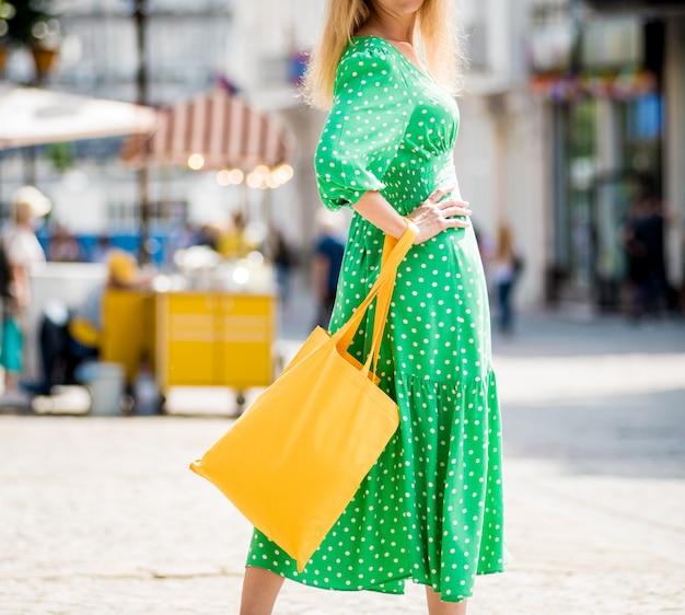 Jeune femme belle avec un sac écologique en lin jaune sur fond de ville
