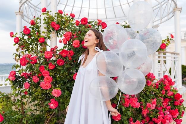 Jeune femme belle souriante avec des ballons à l'extérieur sur des fleurs