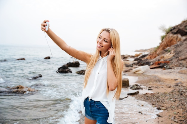 Jeune femme belle souriante écoutant de la musique et faisant selfie en se tenant debout sur la plage rocheuse