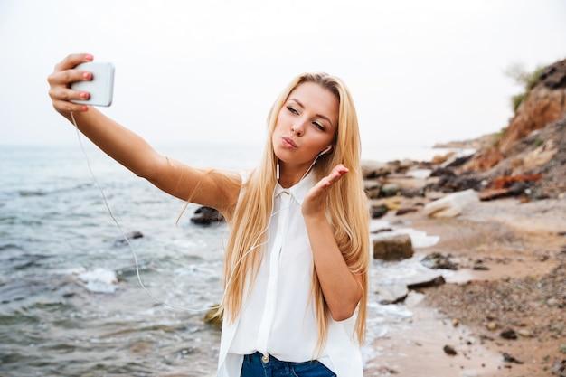 Jeune femme belle souriante envoyant un baiser d'air et faisant selfie en se tenant debout sur la plage rocheuse