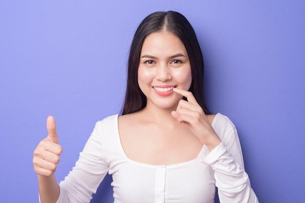 Jeune femme belle souriante montre et pointe ses dents blanches droites saines sur violet