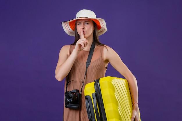 Jeune femme belle voyageur en chapeau d'été avec valise jaune et appareil photo faisant le geste de silence avec le doigt sur les lèvres sur le mur violet