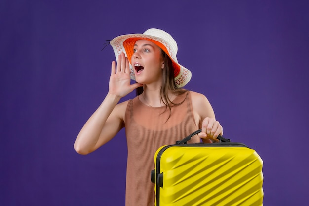 Jeune femme belle voyageur en chapeau d'été avec valise jaune criant ou appelant quelqu'un avec la main près de papillon sur mur violet