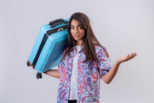 Jeune femme belle voyageur tenant la valise à la recherche de gesticulations confus avec la main et l'expression comme posant une question debout sur fond blanc