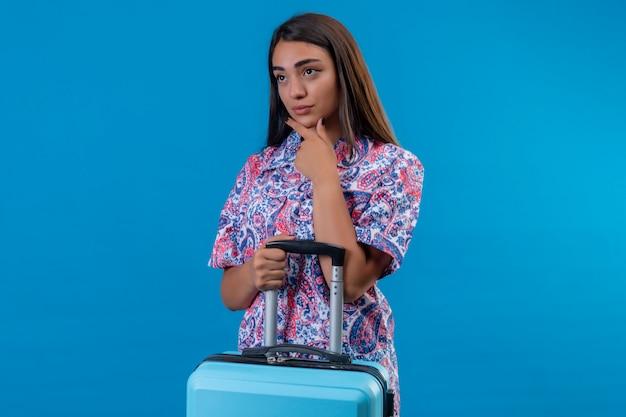 Jeune femme belle voyageur avec valise avec la main sur le menton pensant avoir des doutes, avec une expression pensive sur le mur bleu