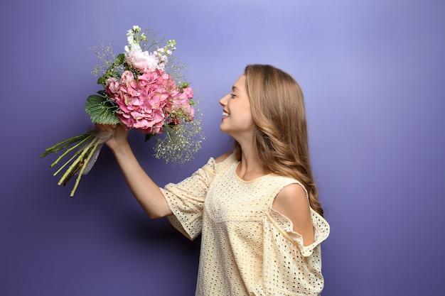 Jeune femme avec de belles fleurs sur une surface de couleur