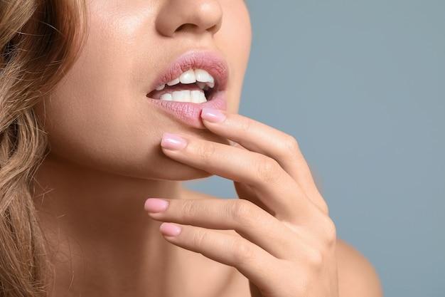 Jeune femme avec de belles lèvres sur fond de couleur, gros plan