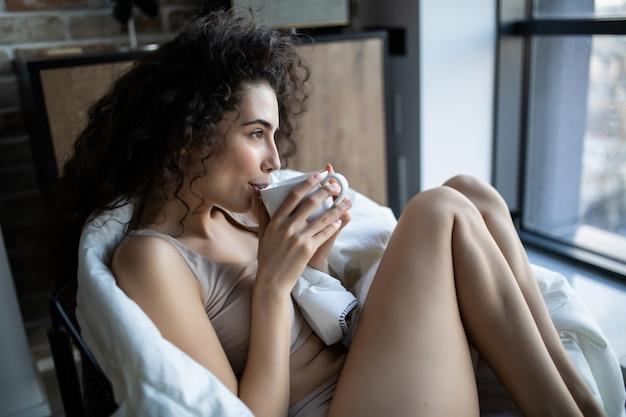Jeune femme bénéficiant d'une tasse de café assis par une fenêtre dans un matin ensoleillé