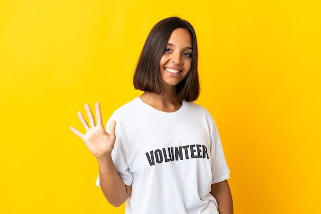 Jeune femme bénévole isolée sur jaune comptant cinq avec les doigts
