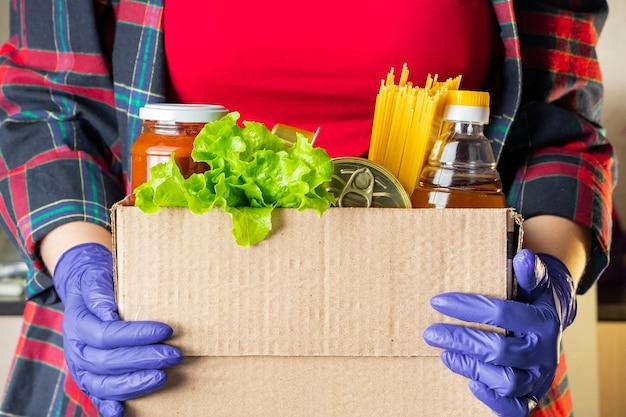 Une jeune femme bénévole tient une boîte de dons avec des denrées alimentaires
