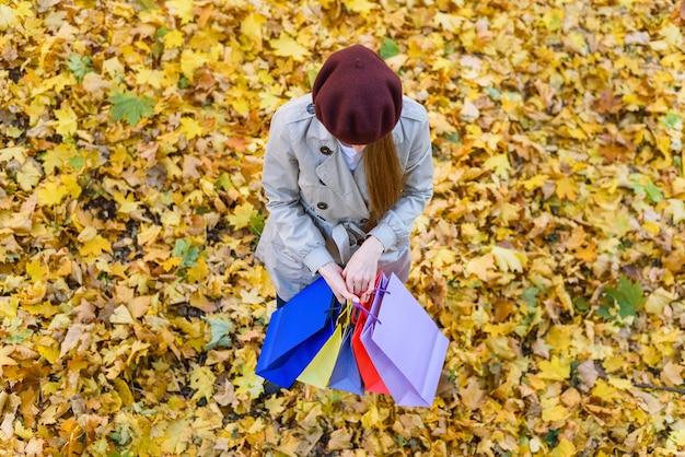 Jeune femme en béret en mains en automne parc. style rétro. vue de dessus.