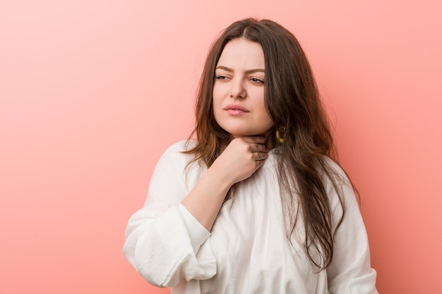 Jeune femme bien roulée caucasienne debout contre le mur rose